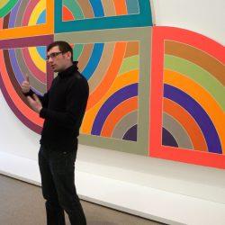 dr Filip Lipiński przed obrazem Franka Stelli, Deutsche Guggenheim
